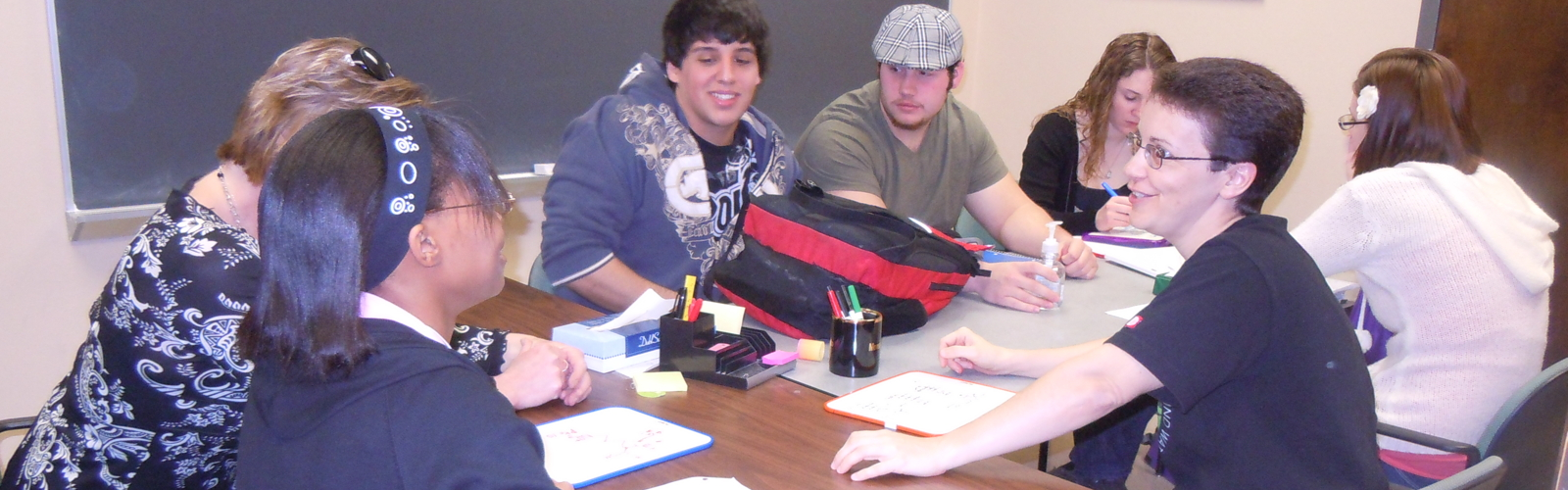 Six students around a table working on problems with an instructor
